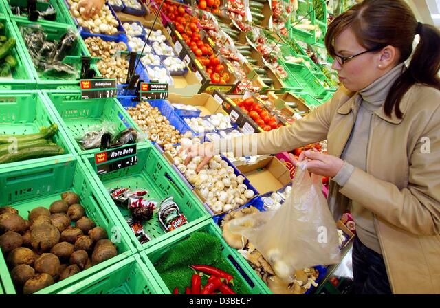 (dpa) - A young lady chooses fresh vegetable in a supermarket in Duesseldorf, Germany, 14 January 2003. Despite - Stock Image