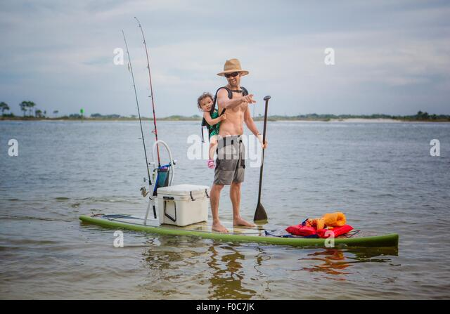 Man and baby daughter standup paddleboarding in the sound, Fort Walton, Florida, USA - Stock-Bilder