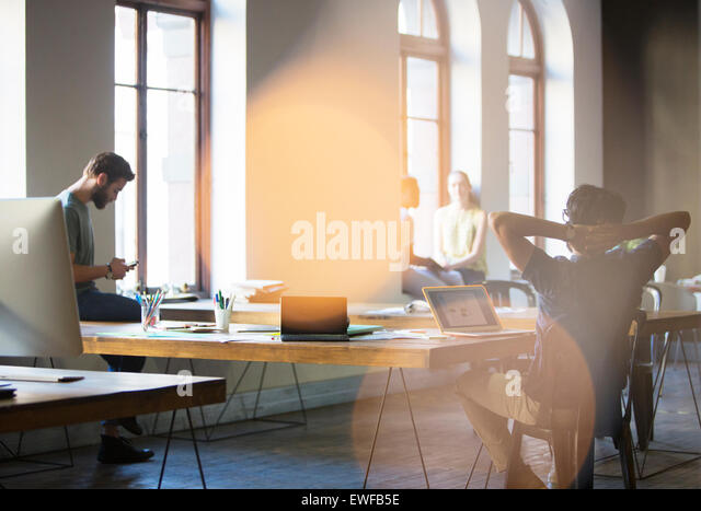 Casual business people working in open office - Stock Image