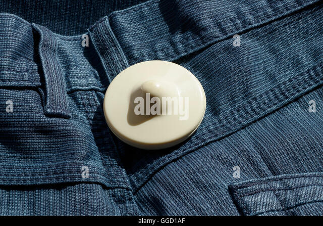 A shop security tag on a pair of trousers - Stock Image