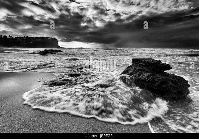 Fast flowing tidal wave overflows sandstone boulder on a sandy Bungan beach of Sydney Northern beaches at sunrise - Stock Image