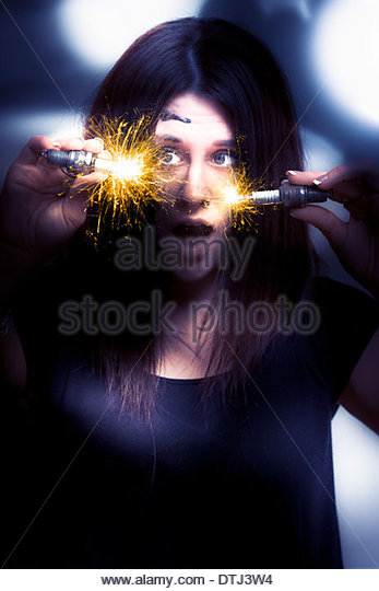 Electric Currents Of Powerful Energy Shoot Out Of Two Spark Plugs Held In The Hands Of A Automotive Electrician - Stock Image