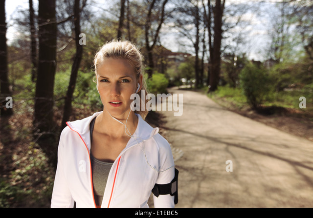 Portrait of pretty young woman in sports clothing wearing earphones while on fitness routine in forest. Young female - Stock Image