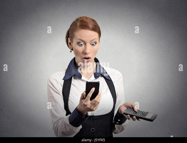 Portrait shocked businesswoman looking on smart phone holding calculator unexpected financial bills charges isolated - Stock Image
