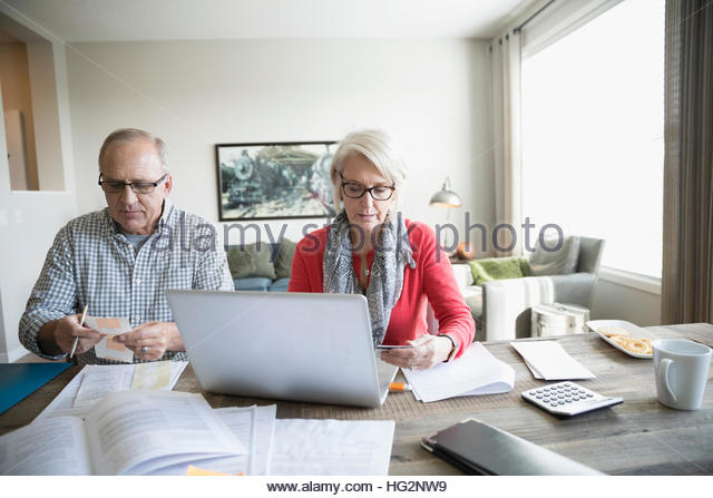 Senior couple with laptop paying bills online in dining room - Stock Image