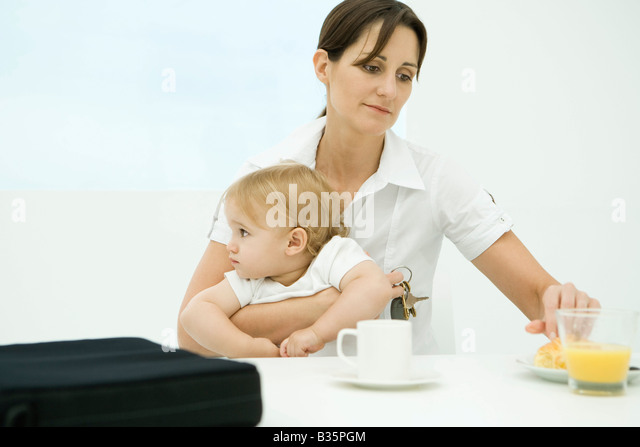 Professional woman sitting at breakfast table, holding toddler and keys - Stock-Bilder
