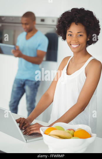 Smiling woman in the kitchen using laptop - Stock Image