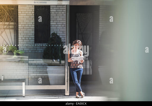 Young woman at bus stop reading newspaper and waiting for bus, New York, US - Stock-Bilder