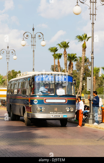Old Bedford bus collecting local workers, Larnaca, Cyprus. - Stock Image