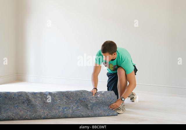 Man unrolling under carpet - Stock-Bilder
