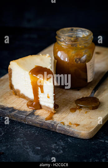 Cheesecake with caramel sauce on wooden chopping board. Close up, selective focus - Stock Image