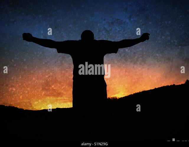 Silhouette of a man with arms stretched out at sunset - Stock Image