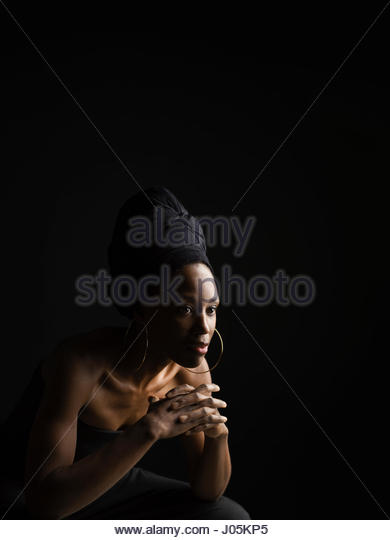 Serious, pensive African American woman in headscarf against black background - Stock Image