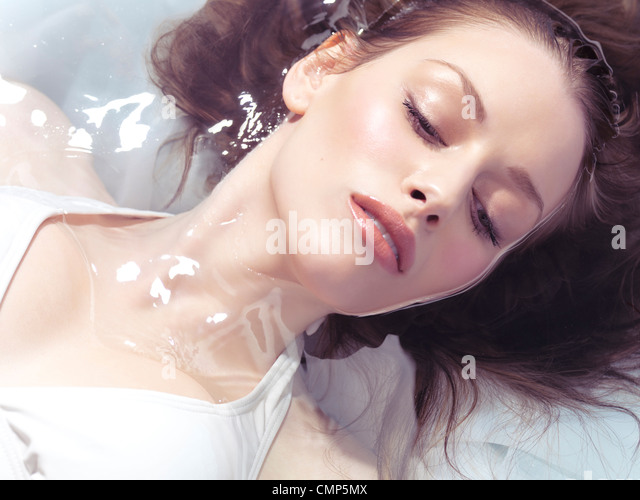 Beauty portrait of a young beautiful woman lying in water - Stock Image