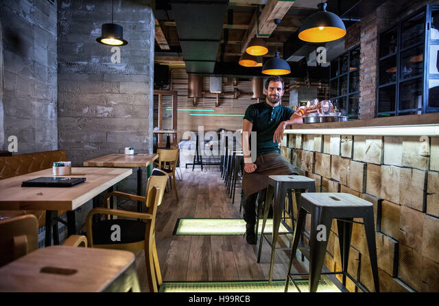 Entrepreneur sitting at bar counter of his coffee shop - Stock-Bilder
