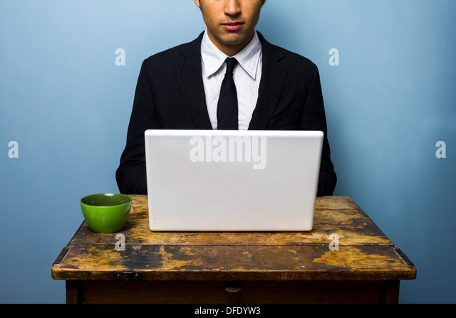 Young businessman drinking coffee and working on his laptop - Stock Image