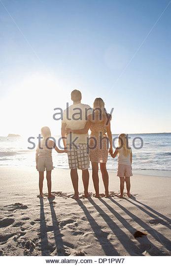 Family on beach holding hands - Stock-Bilder
