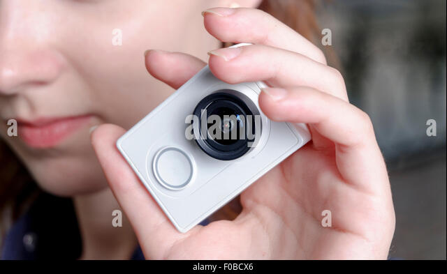Young sporty women with unrecognisable action camera in hands - Stock Image