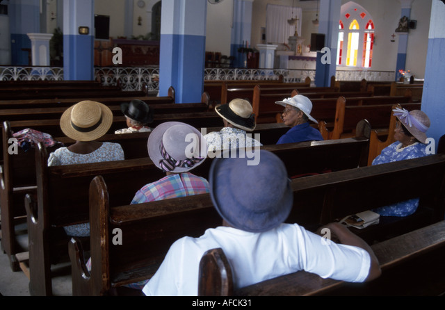 West Indies St. Lucia Soufriere Roman Catholic church Black female members pews - Stock Image