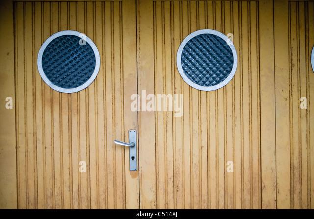 Wooden doors with circular windows - Stock Image