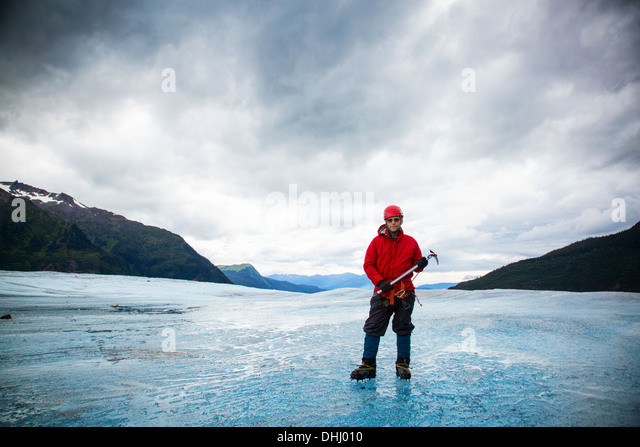 Man with ice pick on Mendenhall Glacier, Alaska, USA - Stock Image