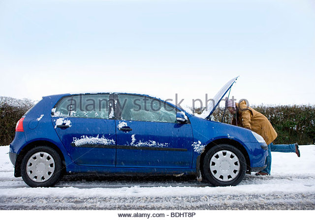 Stranded woman looking at car engine in snow - Stock Image