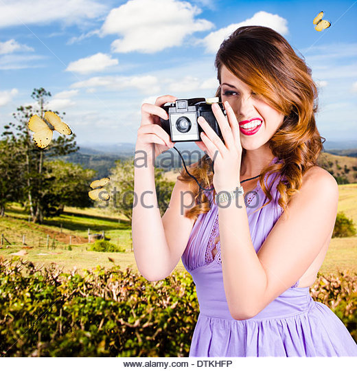 Cute young female wildlife photographer shooting insects and nature with old vintage film camera - Stock Image