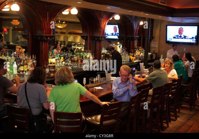 Boston Massachusetts Newbury Street Joe's American Bar & Grill bar pub stools bartender man woman customers - Stock Image
