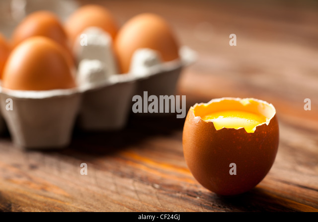 Opened Egg Shell with Yolk on Wood - Stock Image