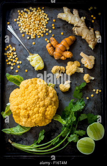 Orange cauliflower and yellow spit peas on pan - Stock Image