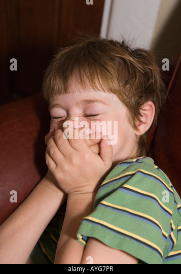 five year old child covering mouth, trying not to laugh, closeup - Stock Image