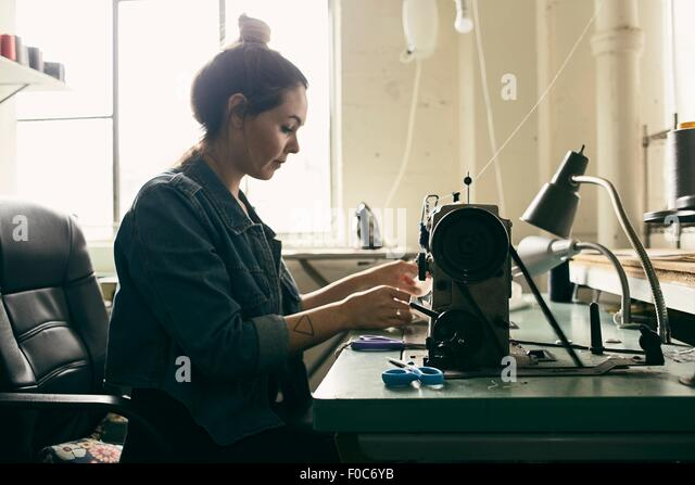 Young female seamstress using sewing machine in fashion studio - Stock Image