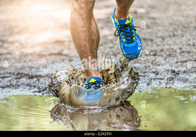 Running man walking in a puddle, splashing his shoes. Cross country trail. Freeze action - Stock Image
