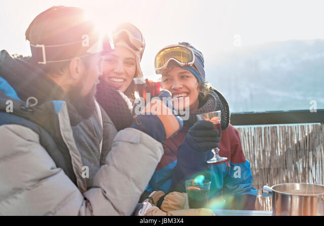 Smiling skier friends drinking cocktails apres-ski - Stock-Bilder