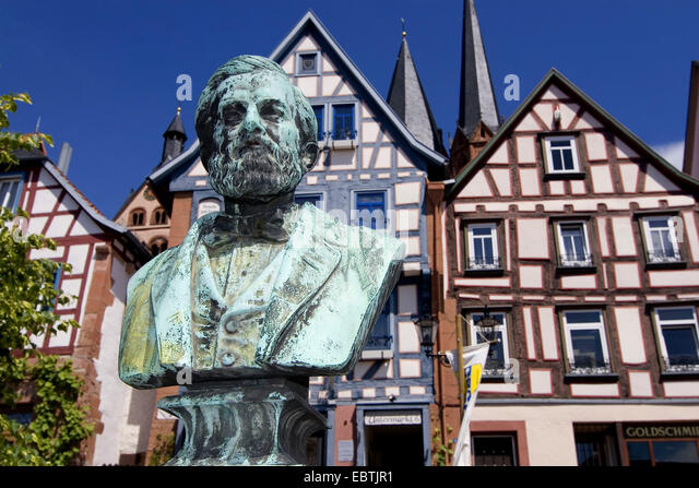 bust of Johann Philipp Reis, the inventor of the telephone, in front of half-timbered houses of the town of his - Stock Image