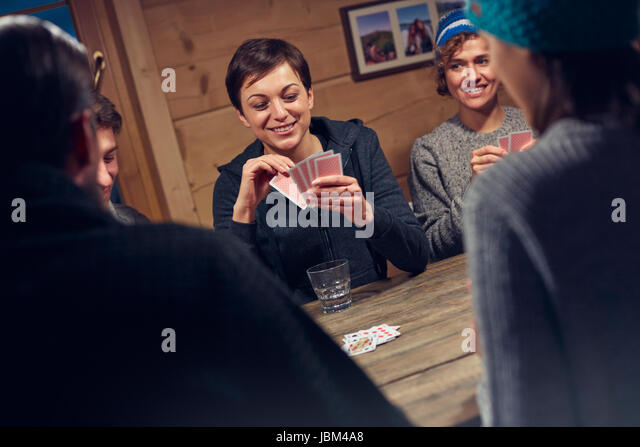 Friends playing cards at cabin table - Stock-Bilder