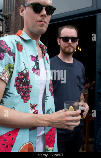 Hackney. Broadway market. Cat and mutton pub. Two men with drinks, one wearing a summer colorful shirt - Stock Image