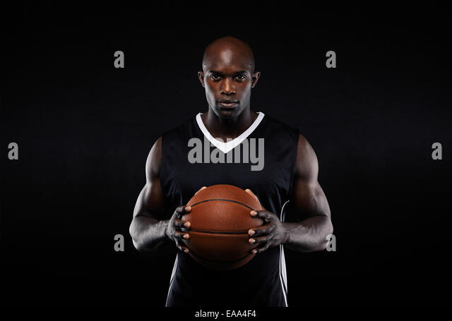 Portrait of muscular young male basketball player in uniform with a basketball posing on black background - Stock Image