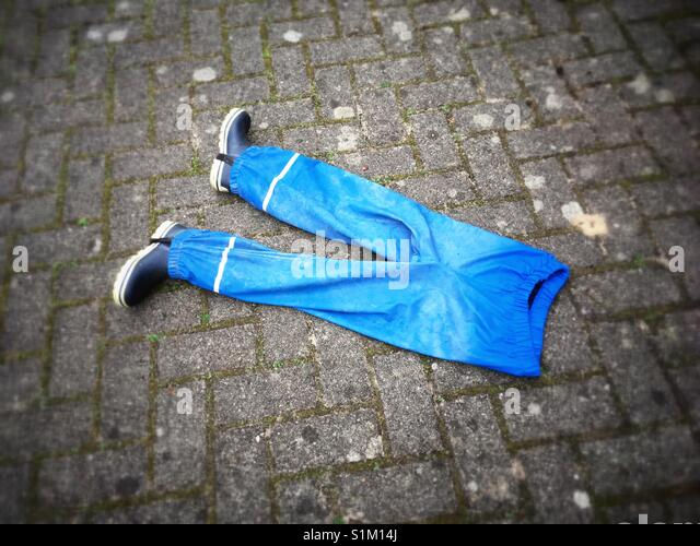 Blue Rain trousers with a pair of wellingtons - Stock Image