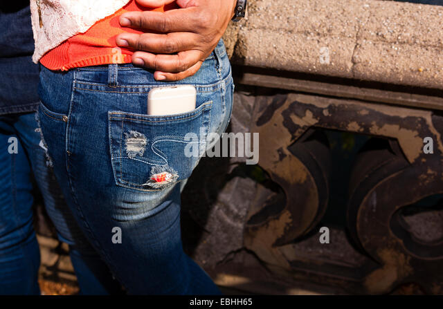 Smartphone in back pocket of jeans - Stock Image
