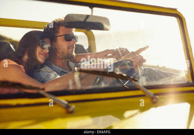 Young man driving car pointing something interesting to his girlfriend. Caucasian couple on summer holiday, Romantic - Stock-Bilder
