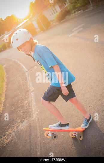 Sweden, Smaland, Anderstorp, Portrait of boy (10-11) riding red shortboard in street - Stock Image