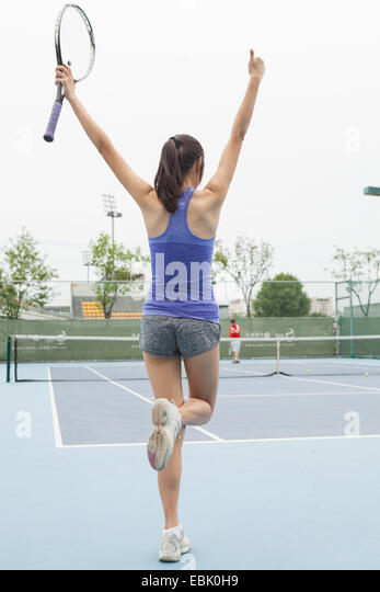Rear view of young female tennis player celebrating on tennis court - Stock Image