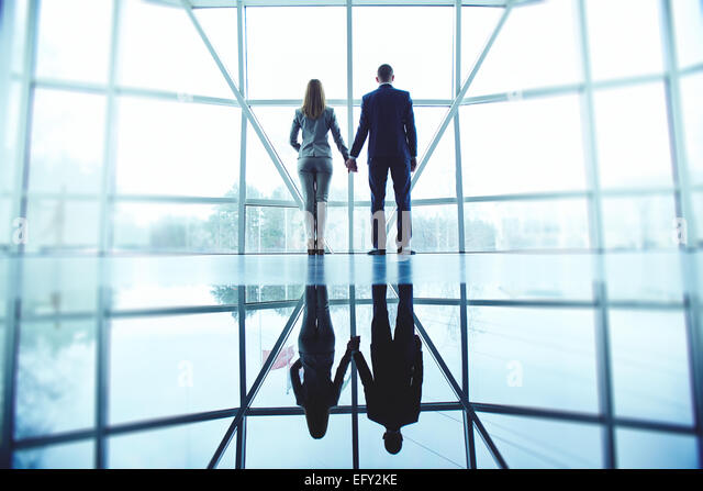 Young man and woman in formalwear holding by hands while standing by office window - Stock-Bilder