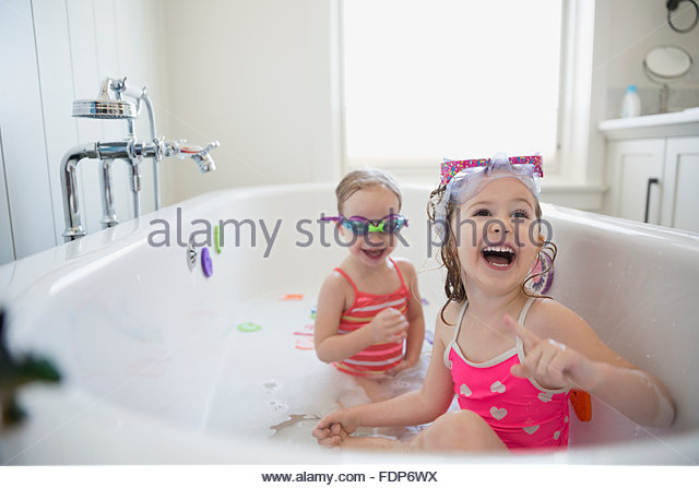 Laughing sisters playing in bubble bath - Stock Image