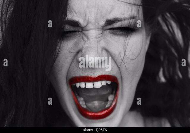 Close-Up Of Angry Woman Shouting With Eyes Closed - Stock Image