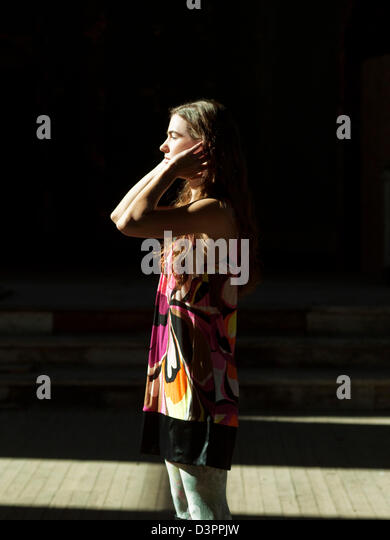 Woman standing in the sunlight - Stock Image