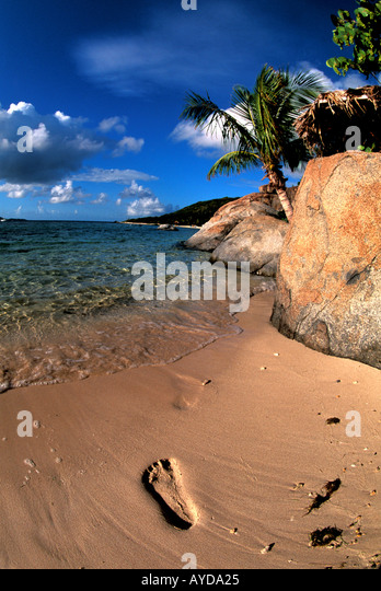one Footprint in sand on Tropical Beach framed by large boulders and palm trees - Stock Image