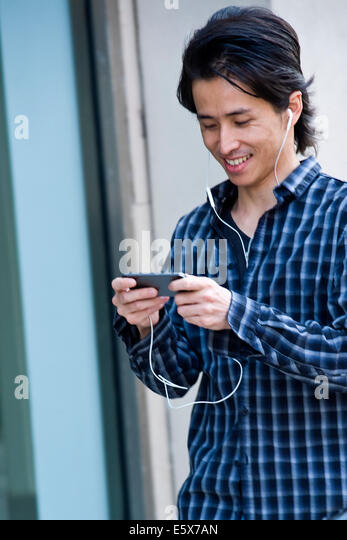 Mid adult man walking down city street selecting music on smartphone - Stock Image