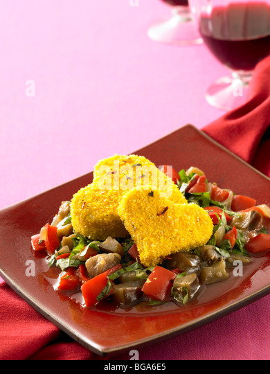 Baked cornmeal crusted tofu hearts with eggplant and red pepper stew - Stock Image